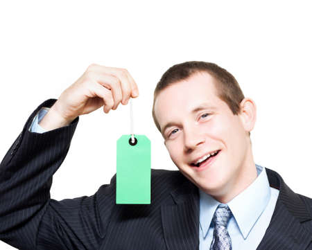persuasive: Laughing young store sales man holding up a blank price tag for your text or contact details in a depiction of sale and commission