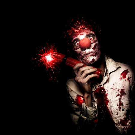 maniacal: Creepy Business Person In Bloody Clown Suit Holding Stick Of Lit Dynamite On Black Studio Background