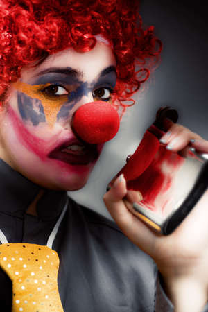 masquerader: Portrait Of A Female Clown With Red Hair And Big Red Nose Holding A Hip Flask In One Hand