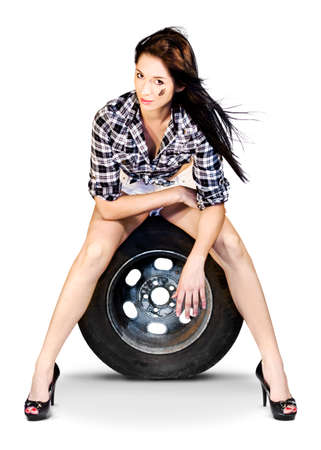 women legs: Road Trip Getaway. Sexy woman in shorts with long shapely legs sitting on a motor car tyre, conceptual studio image on white.