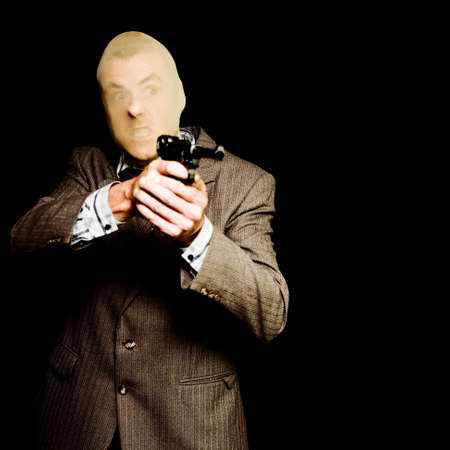 law business: Business man or corporate crook holding hand gun with angry expression isolated on black background