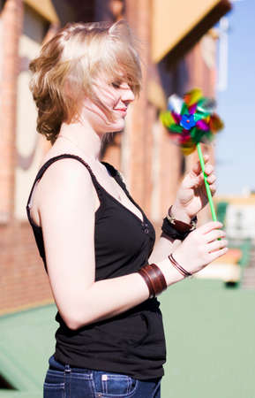 gusty: A Woman Holds On To A Glittery Toy Turbine As The Winds Energy Puts It Into A Colorful Spin
