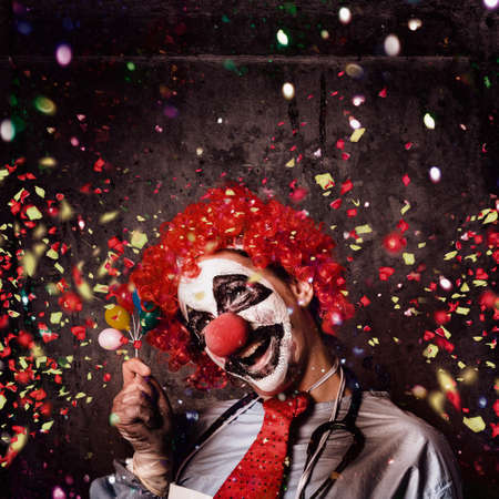 Insane circus clown with smile holding miniature balloons under falling confetti during a birthday party celebration at a hospital ward