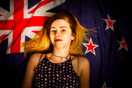 anzac: Lifestyle portrait of a pretty young woman in 20s resting on Australian flag when celebrating the Australia Day national holiday