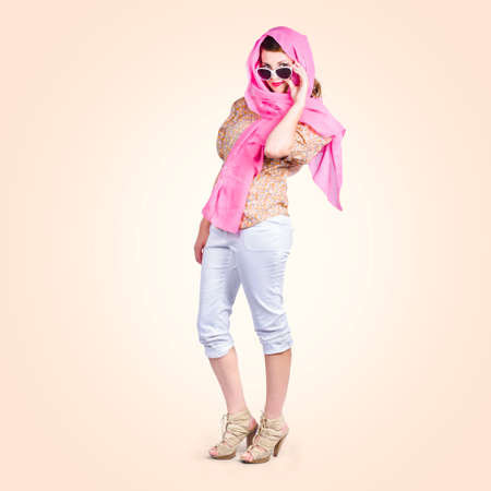 wearing sandals: Full body image of a 1960 pin-up culture girl wearing retro fashion head scarf, white cargo pants and sandals Stock Photo