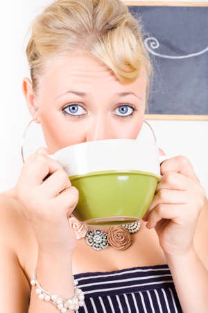 gratified: Young pretty woman with blond hair drinks from a green and white colored cup in a depiction of drinking green tea