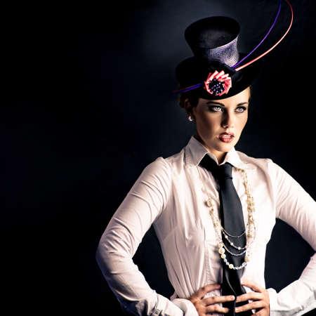 lazo negro: Una actriz vestida con el traje típico de variedades con un sombrero y un lazo fascinator realizar en un escenario oscuro mirando hacia fuera del bastidor a un público invisible