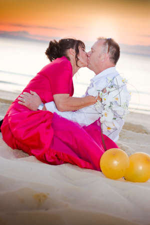 newly wedded couple: Kissing Playful Couple Sit In The Sand On A Tropical Paradise Island Oasis Beach In Wedding Kiss