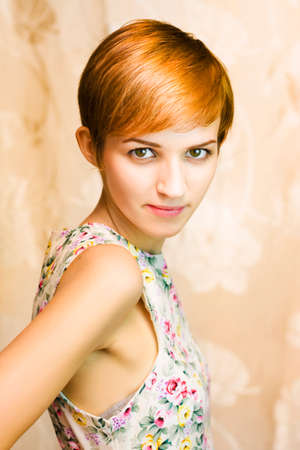 short: short haired girl in floral dress, body away from camera, right hand behind her on a floral brown background