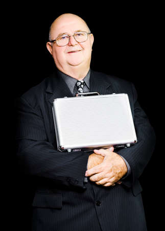balances: An elderly businessman balances his briefcase confidently on his stomach secure in the wealth of his knowledge, conceptual of business leadership through experience