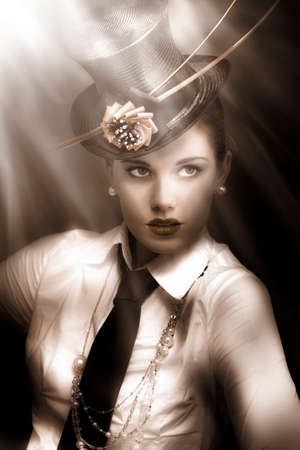 olden day: Woman actress in vaudeville costume of top-hat and tie standing lit up and illuminated under the bright lights of broadway