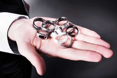 signet: Man displaying a selection of stylish rings on the palm of his hand from plain bands to elegant signet rings