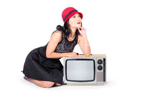 pinup girl: Full length 60s pinup girl wearing fashionable hat, ring and jewellery resting of a vintage television box. Retro fashion communication