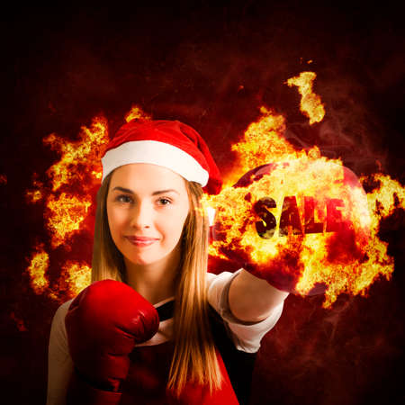 boxing day sale: Scorching christmas shopping concept on the fist of a young boxing woman punching through fire and flames wearing santa hat and boxing gloves. Hot boxing day sale