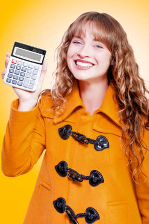 glee: Beautiful woman in a warm orange winter coat grinning with glee holding up a calculator with a blank display on an orange studio background with color gradient Stock Photo