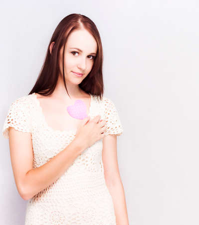 first love: Gentle attractive young girl holding a pastel pink heart to her chest, conceptual of first love with copyspace Stock Photo