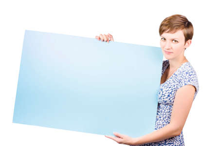 saleslady: Smiling friendly young woman with short neat hair holding a blank blue rectangular placard to the side with copyspace for your text or advertisement, isolated on white Stock Photo