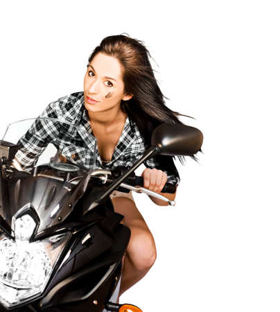 approaching: Attractive brunette woman riding a large motorbike during a race while leaning in to a corner with flying long hair