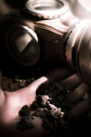 tragedies: Soft Focus On A Dead Mans Hand Buried In Stones And Gravel Next To A Military Issued Gas Mask In A Tragedies Of War Conceptual Stock Photo