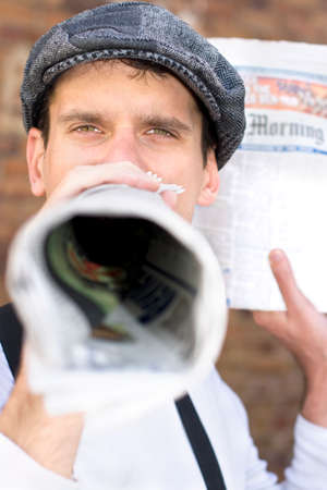 sell: Paper Boy Spruiks The News With A Rolled Up Newspaper Megaphone Stock Photo