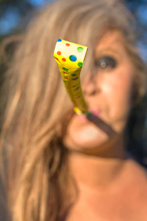 noisemaker: Woman Whistle Blower Celebrates The New Year By Blowing A Party Noisemaker