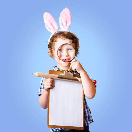 bunny ears: Delightful young boy wearing bunny ears looking through magnifying glass while holding easter shopping wish list