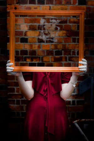 ghostly: Body Of Ghostly Young Woman Holding Empty Picture Frame With Brick Wall Background