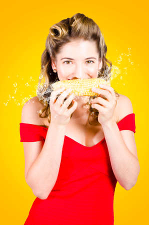 mealie: Fun old fashioned portrait of a retro pinup girl eating corn on the cob with juicy splashes of GMO free goodness. Organic healthy eating