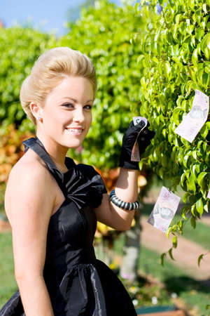 pulling money: A Smiling Wealthy Woman Manages Her Investments By Pulling An Australian 5 Dollar Note From A Money Tree
