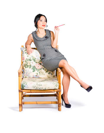 sexy girl smoking: Retro portrait of a beautiful chinese woman sitting on lounge chair with cigarette holder Stock Photo