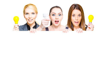 breaking new ground: Three business people holding up light bulbs and blank copy space sign in a advertisement for a innovative idea, insight and business success, isolated on white Stock Photo