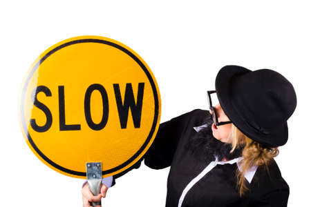 black rimmed: Woman in black homburg trilby hat wearing wide rimmed spectacles and jacket holding a yellow sign saying slow on white