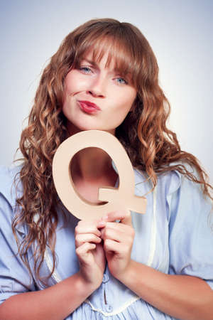 befuddled: Beautiful young woman with a bemused befuddled look thinking while holding capital letter Q in a quest to seek answers from questions Stock Photo