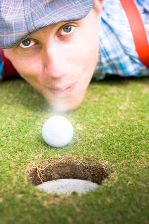 lays down: Person Wearing Flat Cap And Suspenders Lays Down Face First On A Golfing Green To Blow The Ball Into The Hole In A Wacky Madcap Golfing Conceptual Stock Photo