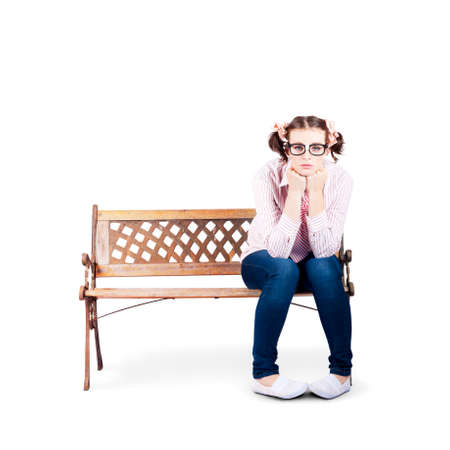 woebegone: Isolated Photograph Of A Sad Lonely Nerdy Woman Sitting On A Park Bench All Alone On White Background Stock Photo