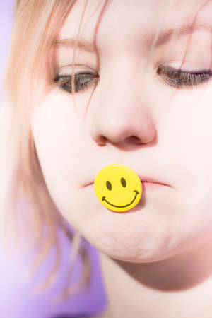 despaired: Sad And Depressed Woman With A Smile Badge In Her Mouth Puts On A Happy Face Stock Photo