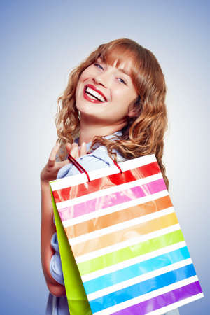 retail therapy: Beautiful smiling woman holding a colourful striped shopping bag over her shoulder filled with viality after a day of successful shopping in a retail therapy concept