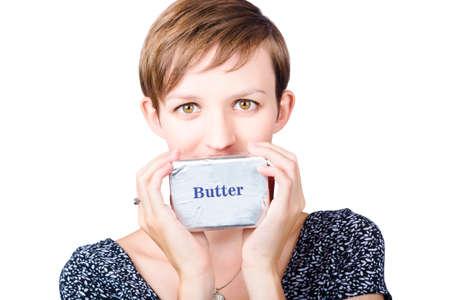grasas saturadas: Hermosa mujer joven sosteniendo un bloque de mantequilla envuelto en papel de plata delante de la boca, aislado en fondo blanco