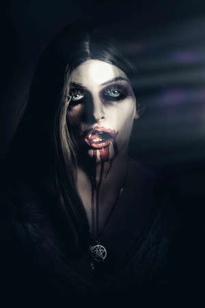 lurking: Psychotic bleeding undead zombie girl licking blood lips when lurking in darkness with opening door light illuminating face.  New Demons