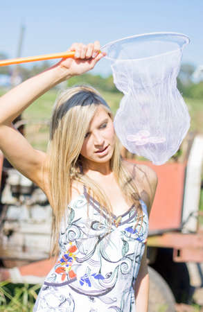 curiously: A Inquisitive Lady Curiously Peers Through A Bug Catching Net To See A Butterfly Inside In A Beautiful Catch