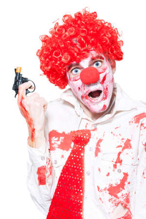 depraved: Evil Clown In Blood Stained Business Outfit Holding Cap Gun During A Halloween Robbery On White Background