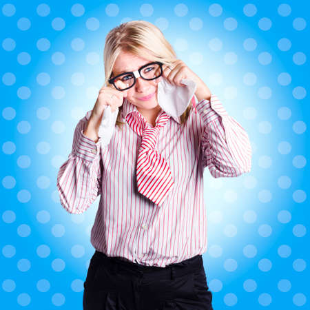 farewell: Depressed nerdy businesswoman holding tissues in hand when crying on blue dot background. Business trouble concept Stock Photo