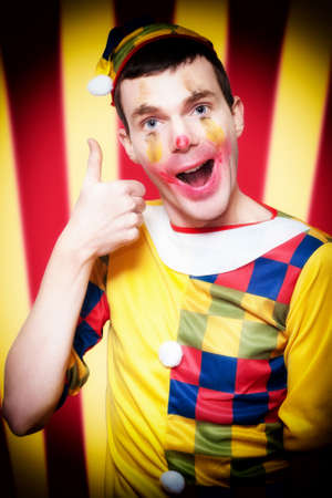 Playful Smiling Circus Clown Standing Inside Bigtop Tent Giving Thumbs Up For Good Entertainment While Gesturing A Trapeze Act Above