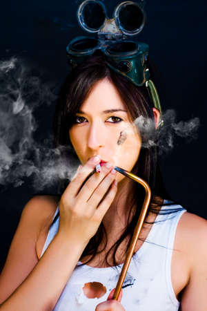 blowtorch: Attractive woman with welding goggles smoking a cigarette off the flame of a welding torch in a industrial fumes conceptual