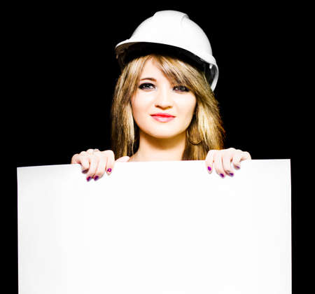 engineering design: Isolated photograph of a female architect wearing hard hat while holding a blank white sign in hands in a design your own property blueprint with copyspace Stock Photo