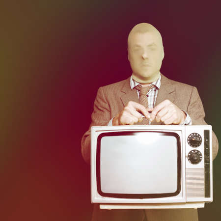 trespasser: Burglar in a stocking mask and suit stealing an old retro television set as he tries to slip quietly away without being detected during a breaking and entry house robbery Stock Photo