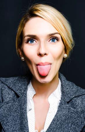 irrespeto: Mujer de negocios Cheeky sacando la lengua como un gesto de falta de respeto o en una broma de humor juguetón