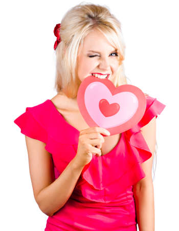 heartbreaker: A delicious young blonde woman winking while biting into a cardboard heart. Heartbreaker concept