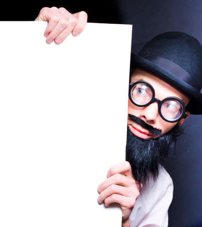 peering: Humorous Image Of A Stereotypical Bearded Professor Wearing Glasses And A Hat Peering Inquisitively Around A Blank Copy Space Board For Your Scientific Text Stock Photo
