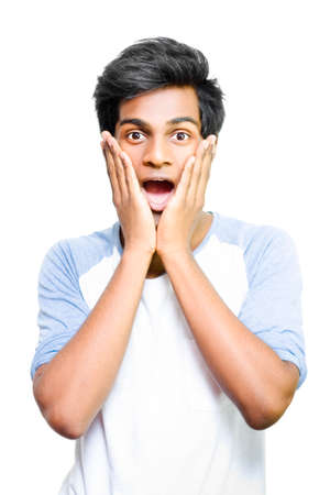 unawares: Excited young Asian man with hands to face and surprised expression on white background Stock Photo